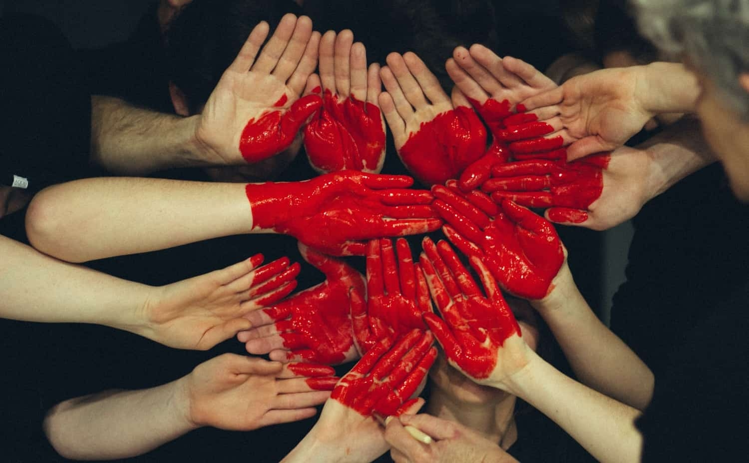 Hands together painted as a red heart to represent togetherness.